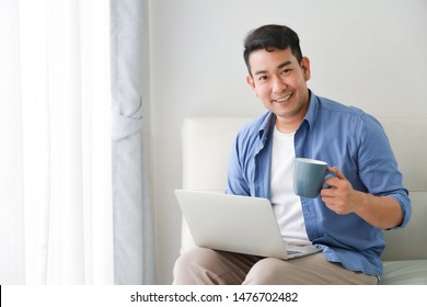 Asian handsome man working with laptop computer and drink coffee in living room happy and smile face