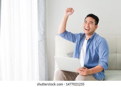 Asian handsome man working with laptop computer   in living room happy and smile face