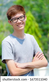 Asian handsome teenage boy wearing glasses standing arms crossed, Portrait cheerful hipster young man are looking and smile with a happy face at park in Thailand