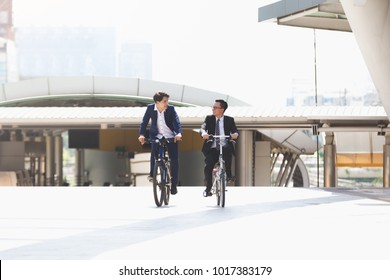 Asian handsome young businessmen talking while riding bicycles in city