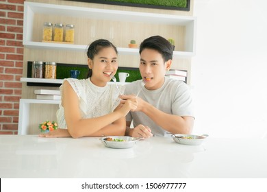 A asian handsome young man and asian beautiful young woman feeding food. A asian man 24 years old and woman 24 years old eating breakfast
