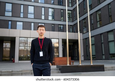 Asian handsome young man with a lanyard standing in front of office buildings and hands in pocket