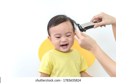 Asian happy baby getting his first haircut by mother during Covid-19 coronavirus pandemic, self-quarantine and social distancing.