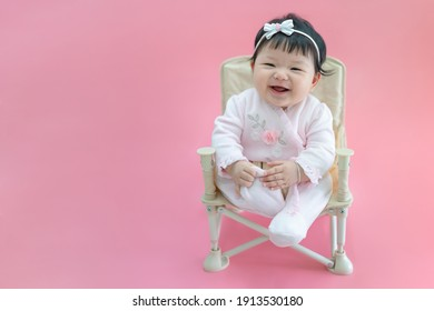 Asian happy baby smiling and sitting on a chair in pink color background. Cute 6 months baby wearing pink cloth with copy space use as concept of valentine, love, baby or kid department in hospital.
