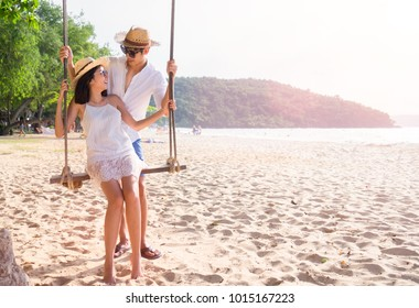 Asian happy couple in summer on the beach in a tropical place. lovers in vacation in an idyllic nature scene sharing positive feelings and emotions.