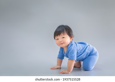Asian happy cute baby smiling, sitting on gray background. 6 months baby in blue cloth on copy space as concept of bedroom, development, health, mood and motion of baby and kid department in hospital