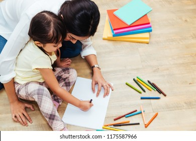 Asian happy family child kid girl kindergarten drawing or painting art and education learning together beautiful parent mom teacher at interior room home