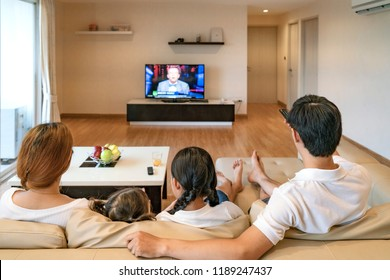 Asian happy family sitting and watching television at home and spent quality time together. Asian family, Family activity, Social Distancing, vacation day, holiday, happiness or lifestyle concept