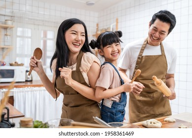 Asian happy family stay at home in kitchen spend time together baking bakery and foods. little kid with parents, father and mother dancing and laughing, enjoy parenting activity relationship in house. - Shutterstock ID 1958361469