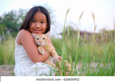 Asian happy girl holding her cat on grass field near the roadside. Happy time and relax with her cat. I love my kitten. Outdoor portrait on nature background.