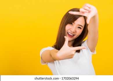 Asian happy portrait beautiful cute young woman standing wear t-shirt hands and finger making frame gesture camera for photography looking to camera, studio shot on yellow background with copy space
