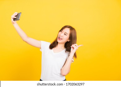 Asian happy portrait beautiful cute young woman teen smiling standing wear tshirt mrak selfie photo, video call on smartphone, point finger back isolated, studio shot yellow background with copy space