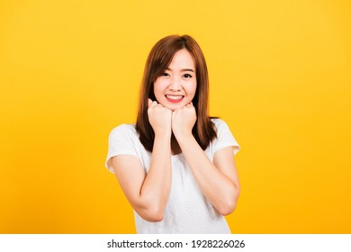 Asian happy portrait beautiful cute young woman teen stand wear t-shirt happy expression fist pressed together under chin looking to camera isolated, studio shot on yellow background with copy space