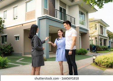 Asian happy smile young couple take keys new big house from real estate agent or realtor in front of their house after signing contract agreement, concept for real estate.