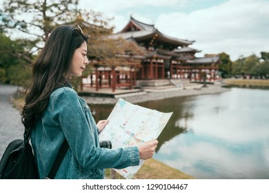 asian happy tourist standing on stone road consulting guidebook in valley of the temples. young girl backpacker with sunglasses visit byodo in with paper map. beautiful nature view lake pond.