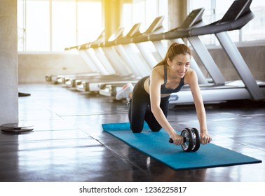 Asian happy woman doing workout and exercise with roller wheel at the gym center,Individual sport