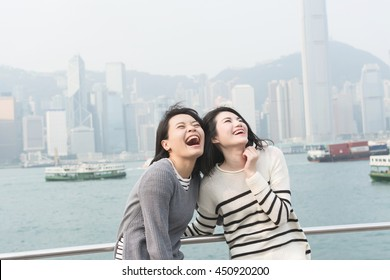 Asian happy young girls traveling at Victoria harbor, Hong Kong, Asia.