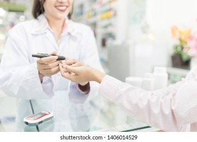 asian healthcare worker use glucometer screening patient in hospital, pharmacist holding hand of patient and keep blood exam to diabetic screening, adult health promotion