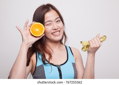 Asian healthy girl on diet with orange fruit and measuring tape on white background