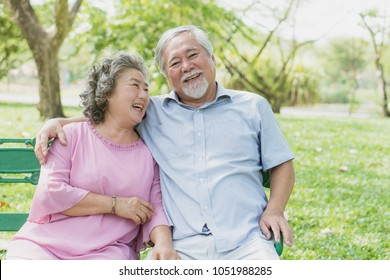 Asian healthy senior couple relaxing seated in the park together.