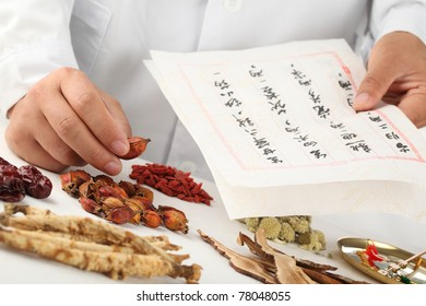 Asian herbalist make a prescription,Chinese characters are names for the herbs.