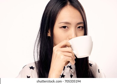 The Asian is holding a mug.