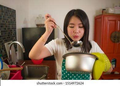 Asian home cook girl lifestyle portrait . Young happy and beautiful Chinese woman in kitchen apron and glove holding cooking pot excited and satisfied preparing soup delighted with delicious taste