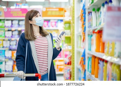 asian homemaker wearing face mask and gloves is using smart phone to check shopping list while buying cleaning supplies at grocery store during virus epidemic outbreak