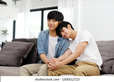 Asian homosexual male lgbt couple, Young asian gay man holding hands with happiness while sitting in home living room, homosexual and lgbt lifestyle concept