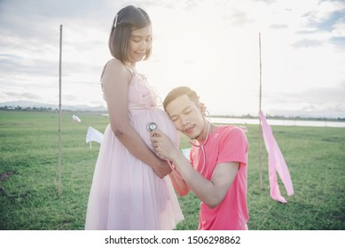 Asian husband use Stethoscope listen to unborn baby heartbeat in his wife belly. Asian Married couple and family concept.