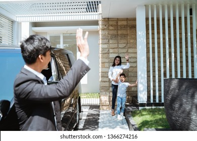 asian husband waving goodbye to his wife and child before going to work