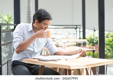 Asian Indian business man reading newspaper while drinking a cup hot milk tea during lunch hour at cafeteria.