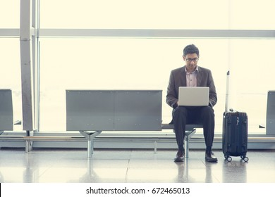 Asian Indian business man sitting on chair and using laptop while waiting his flight at airport.