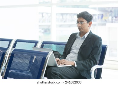 Asian Indian business man waiting his flight at airport, sitting on chair and using laptop.