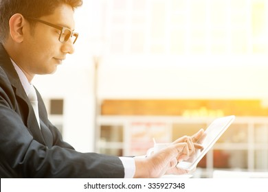 Asian Indian business people using tablet pc at cafe, relaxing with a cup of coffee. India male business man, modern office building with sunlight as background.