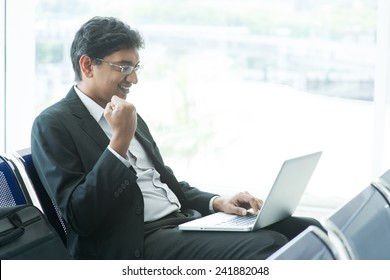 Asian Indian businessman sitting on chair and using laptop while waiting his flight at airport.