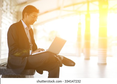 Asian Indian businessman using laptop computer while waiting train at railway station.