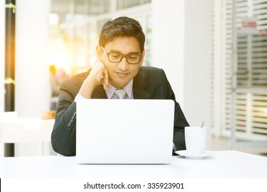 Asian Indian businessman using a laptop or notebook computer at cafe, with a cup of coffee. India male business man, modern building with beautiful golden sunlight as background.