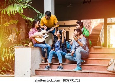 Asian Indian college students playing music with guitar while sitting in campus on stairs or over lawn - Shutterstock ID 1839791752