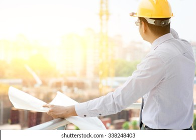 Asian Indian male site contractor engineer with hard hat holding blue print paper looking away inspecting progress at construction site, crane with golden sunlight at the background.
