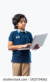 Asian Indian school kid holding and using laptop while standing against white background