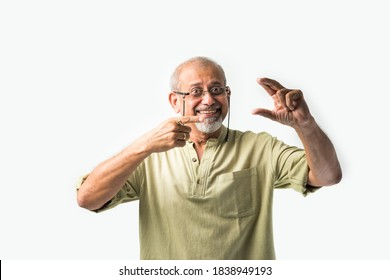 Asian Indian senior or old man presenting empty space, standing isolated against white background