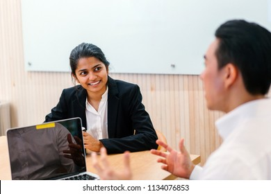 An Asian Indian woman is having an interview for a job in a meeting room during the day. Her interviewer is a Chinese man.