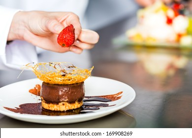 Asian Indonesian chef along with other cooks in restaurant or hotel kitchen cooking, finishing a dish or plate for dessert
