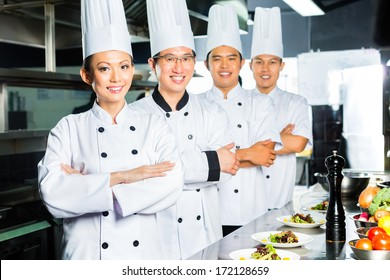 Asian Indonesian and Chinese chefs along with other cooks in restaurant or hotel commercial kitchen cooking, finishing dish or plate