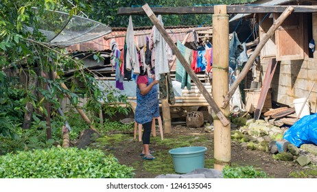 Asian, Indonesian women people washing clean loundry and hanging dry clothes in the sun at front of old classic wooden retro house with satellite dish.