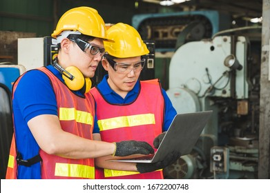 Asian industrial workers are discussing project work in large industrial plants with laptops.