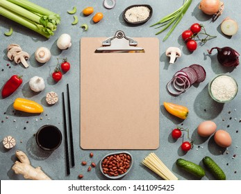 Asian ingredients and empty clipboard. Various of Chinese cooking ingredients and chopsticks on gray stone background. Asian food recipes concept. Copy space for text. Top view or flat lay.