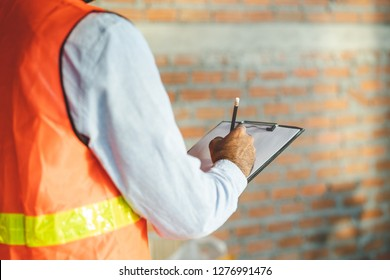 Asian inspector checking structure of new property and taking note in the clipboard for review and fix the house before sell to client