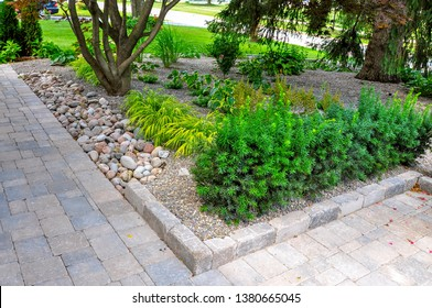 Asian inspired landscaping features various textures and types of plants and natural stone, and tumbled paver edging to help retain the grade.